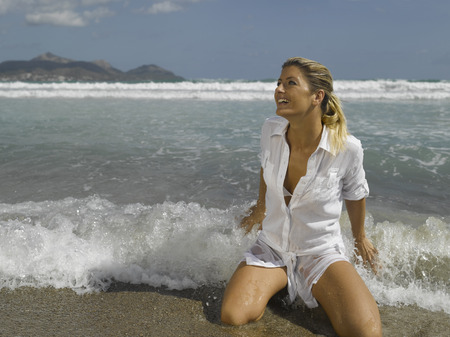 Mid adult woman kneeling on the beach LANG_EVOIMAGES