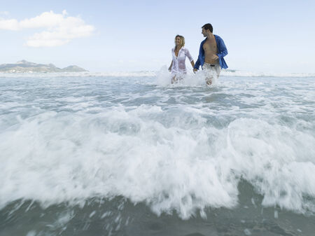 mid adult couple: Mid adult couple running on the beach