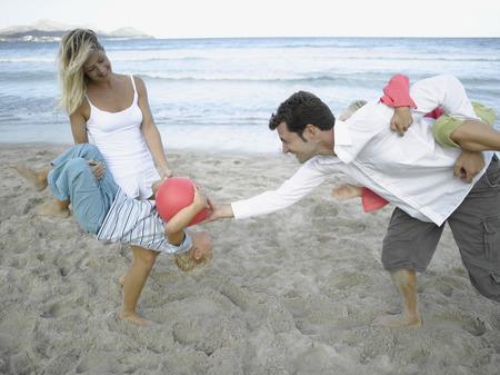 mid adult couple: Mediados de adultos jugando con sus hijos en la playa