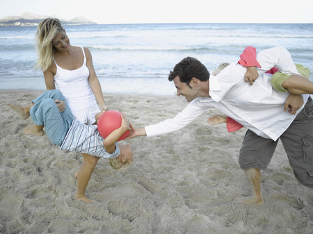 mid adult couple: Mid adult couple playing with their children on the beach
