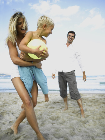 two piece swimsuit: Woman holding her son with a man standing behind him on the beach