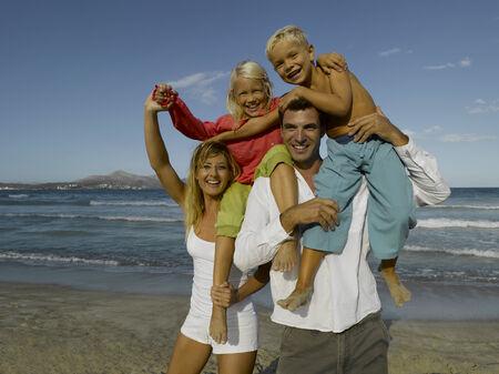 mid adult couple: Retrato de una pareja de mediana edad que lleva a sus dos hijos en sus hombros