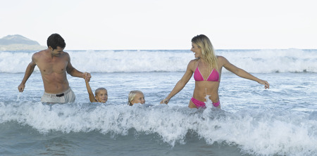 bikini couple: Mid adult couple and their children in the sea LANG_EVOIMAGES