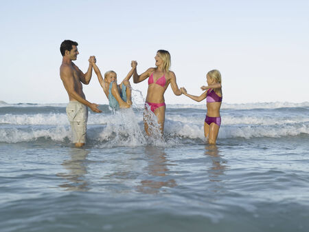 bikini top: Mid adult couple and their two children in the sea