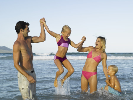 mid adult couple: Mid adult couple and their two children in the sea