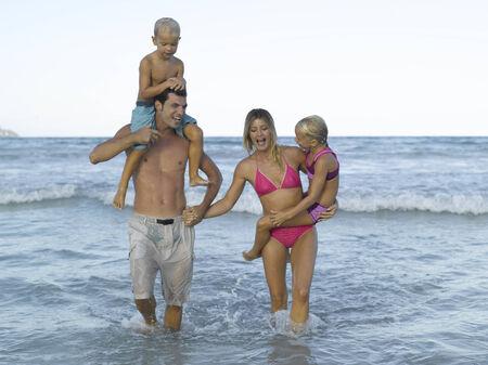 mid adult couple: Pareja de mediana edad y sus dos hijos en el mar