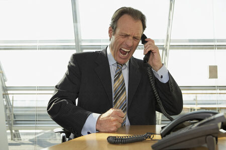 Businessman talking on the telephone and shouting Stock Photo