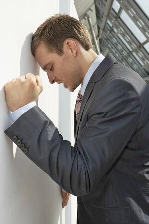 puños cerrados: Perfil lateral de un hombre de negocios apoyado en una pared y mirando deprimido