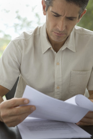 Man looking concerned reading documents