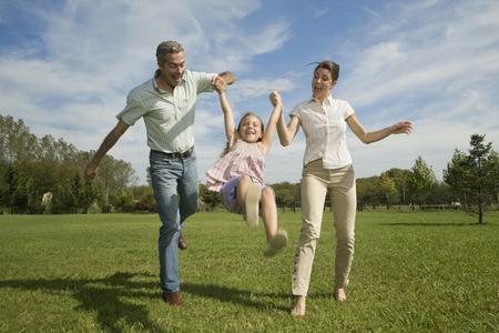 Family swinging daughter in air