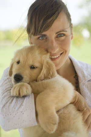 wind blown hair: Woman holding puppy