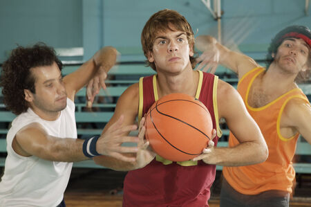 young men: Three young men playing basketball