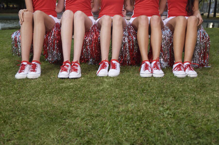low section view: Low section view of five cheerleaders sitting side by side