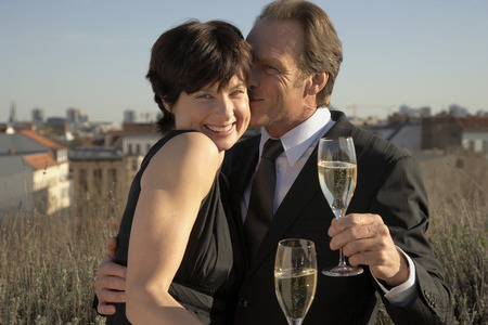 flute structure: Mature man kissing a mature woman and holding a champagne flute