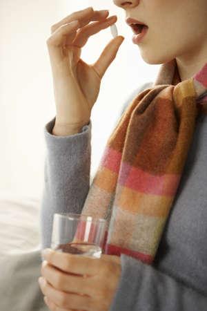 tomando refresco: Perfil lateral de una mujer adulta mediados de tomar una píldora LANG_EVOIMAGES