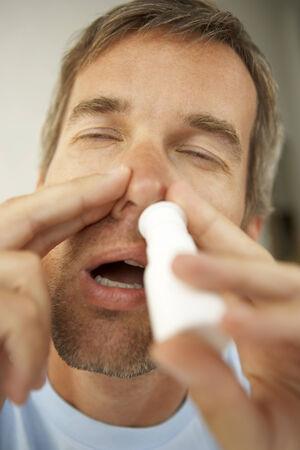 mid adult man: Primer plano de un hombre de mediana edad que usa el aerosol nasal