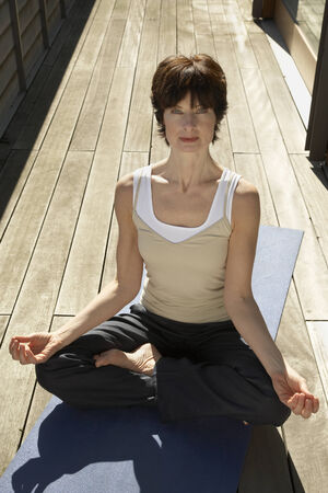 Portrait of a mature woman sitting in a lotus position Stock Photo