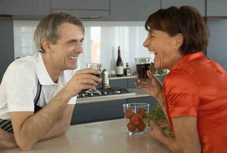 mid adult couple: Pareja de mediana edad la celebraci�n de vasos de vino tinto