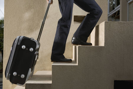 lower section: Person pulling luggage up stairs