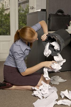 wastepaper basket: Businesswoman looking in a wastepaper basket LANG_EVOIMAGES