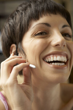 hands free device: Close-up of a young woman wearing a hands free device and smiling LANG_EVOIMAGES