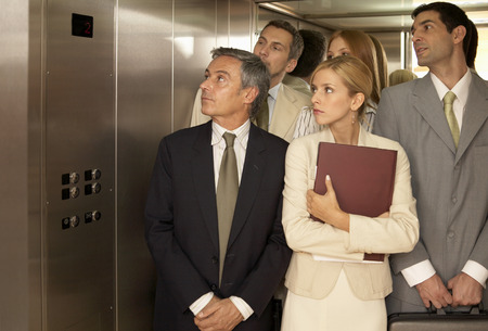 elevator: Five business executives in an elevator