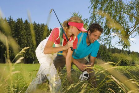 mid adult couple: Mid adult couple searching a golf ball in bush