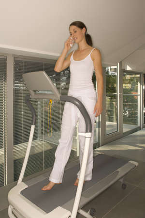 off the shoulder: Woman walking on treadmill LANG_EVOIMAGES