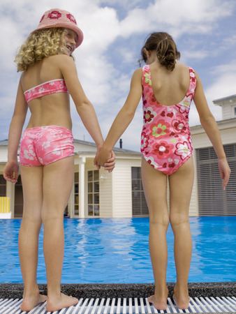 girls holding hands: Girls holding hands near pool