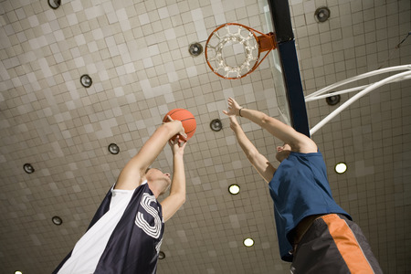 Low angle view of two young men playing basketball