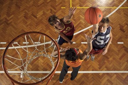 basketball hoop: High angle view of three young men playing basketball