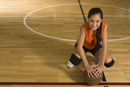 kneepad: Portrait of a young woman holding a basketball and smiling LANG_EVOIMAGES