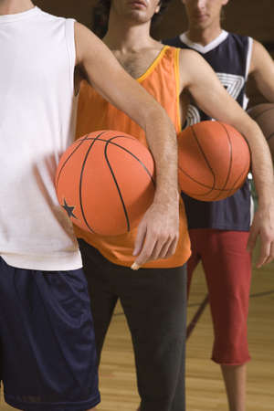 men standing: Three young men standing in a court and holding basketballs LANG_EVOIMAGES