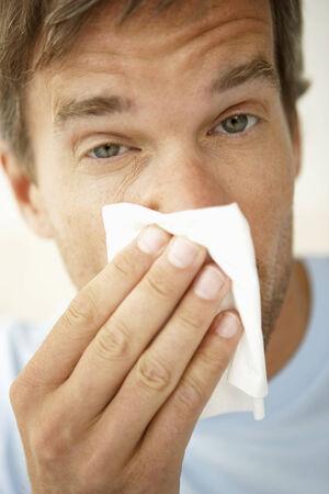 mid adult man: Primer plano de un hombre de mediana edad que sopla la nariz LANG_EVOIMAGES