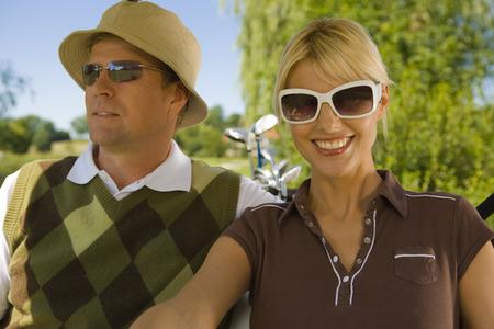 mid adult couple: Primer plano de una pareja de mediana edad sentado en un carrito de golf y sonriendo
