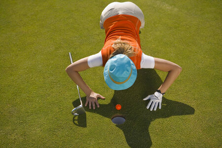 judging: High angle view of a mid adult woman judging a golf ball on a golf course