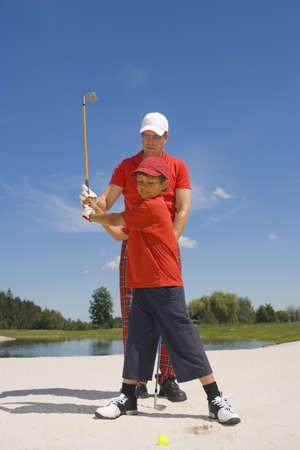 mid adult man: Hombre de mediana edad que da el entrenamiento de golf para su hijo