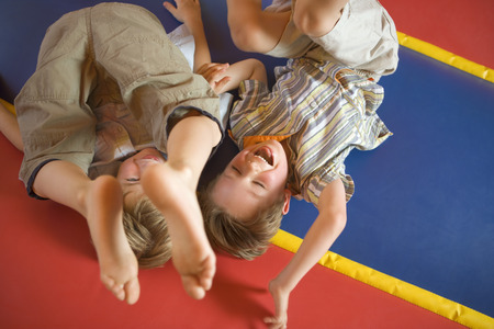 boy barefoot: High angle view of two boys playing on an inflatable bouncy castle