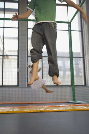 low section view: Low section view of a boy with a girl jumping on a trampoline