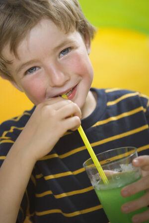 drinking straw: Ritratto di un frullato ragazzo bere con una cannuccia