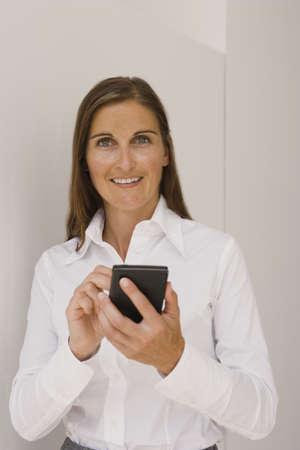 datos personales: Retrato de una mujer de mediana edad el uso de un asistente de datos personales y sonriendo