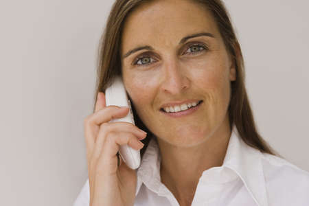 cordless phone: Portrait of a mid adult woman talking on a cordless phone and smiling