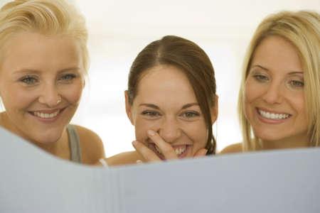 off shoulder: Close-up of three women reading LANG_EVOIMAGES