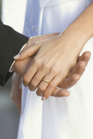 european ethnicity: Detail of bride and groom holding hands LANG_EVOIMAGES