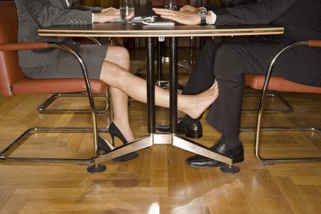 테이블 아래 footsie를 재생하는 기업인