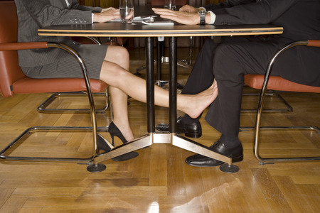 Businesspeople playing footsie under table Imagens