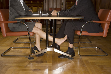 Businesspeople playing footsie under table Stock Photo