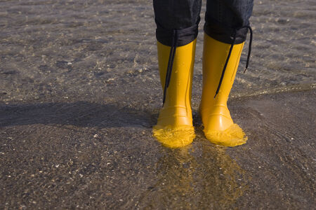european ethnicity: Detail of yellow boots standing in water at the beach LANG_EVOIMAGES