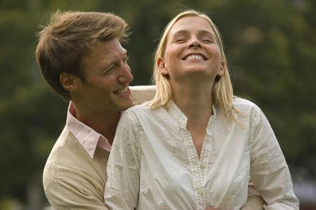 mujer de espaldas: Mediados de hombre adulto que abrazan una mujer de mediana edad por detr�s y sonriendo LANG_EVOIMAGES