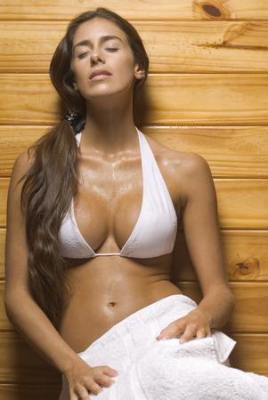 sauna nackt: Junge Frau lehnt gegen eine Holzwand in der Sauna